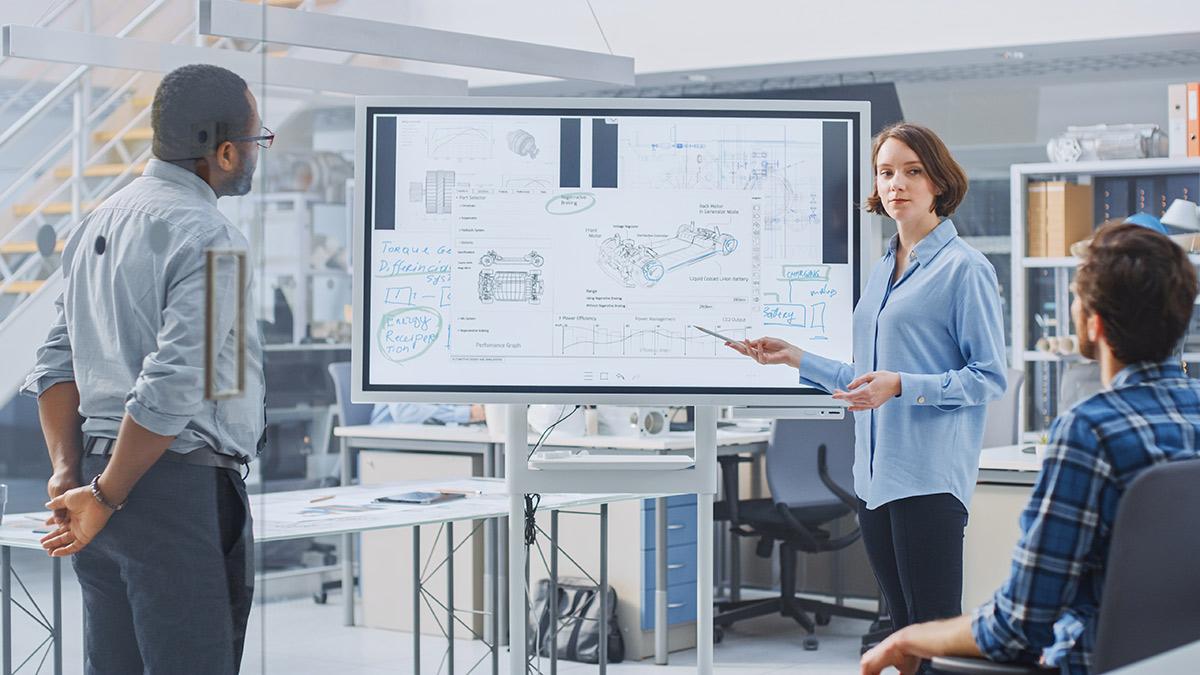 Frau referiert auf digitalem Whiteboard im Büro